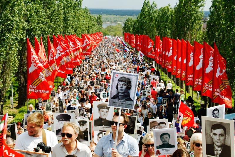 Optocht van plaatselijke bevolking met foto's van hun verwanten in Onsterfelijk Regiment op jaarlijkse Victory Day op Mamaev-Heuv stock fotografie
