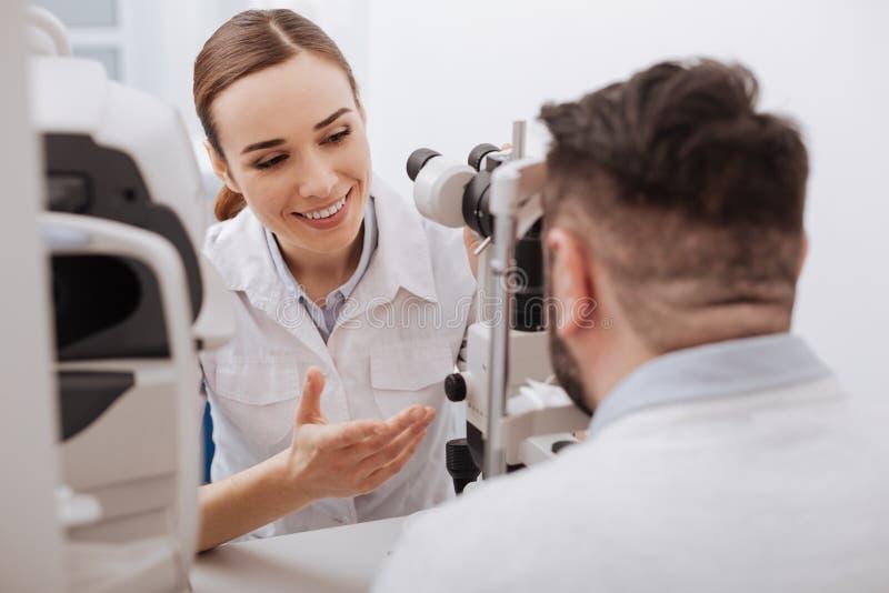 Optométriste amical avec plaisir agissant l'un sur l'autre avec son patient image stock