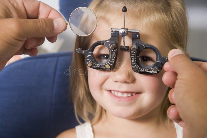 Optométriste dans la chambre d'examen avec la jeune fille photographie stock libre de droits
