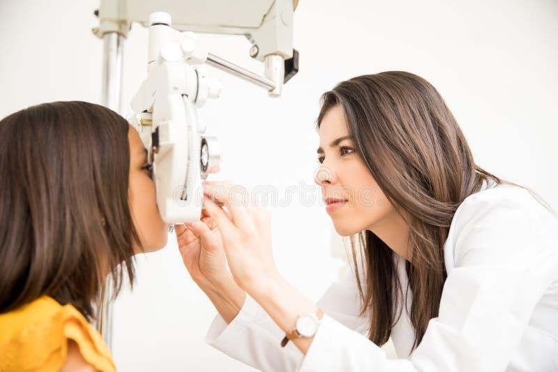 Optométriste faisant l'essai de vue pour la patiente de fille d'école photographie stock libre de droits