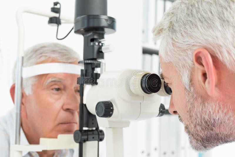 Optométriste faisant l'essai de vue pour le patient supérieur photographie stock libre de droits