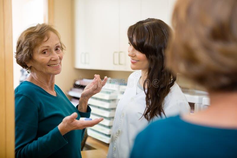 Optométriste Looking At Woman tenant le verre de contact photo stock