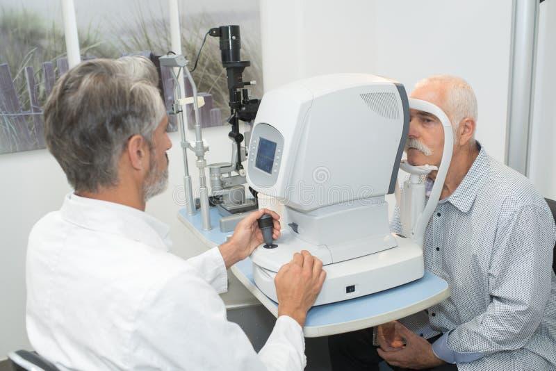 Optométriste masculin faisant l'essai de vue pour le vieux patient photo stock