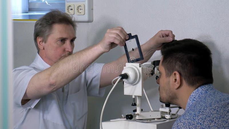 Optométriste supérieur faisant l'essai de vue pour le patient image stock