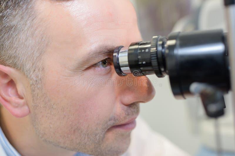 Optometriker, der Sichtfeldversuch durchführt lizenzfreie stockfotografie