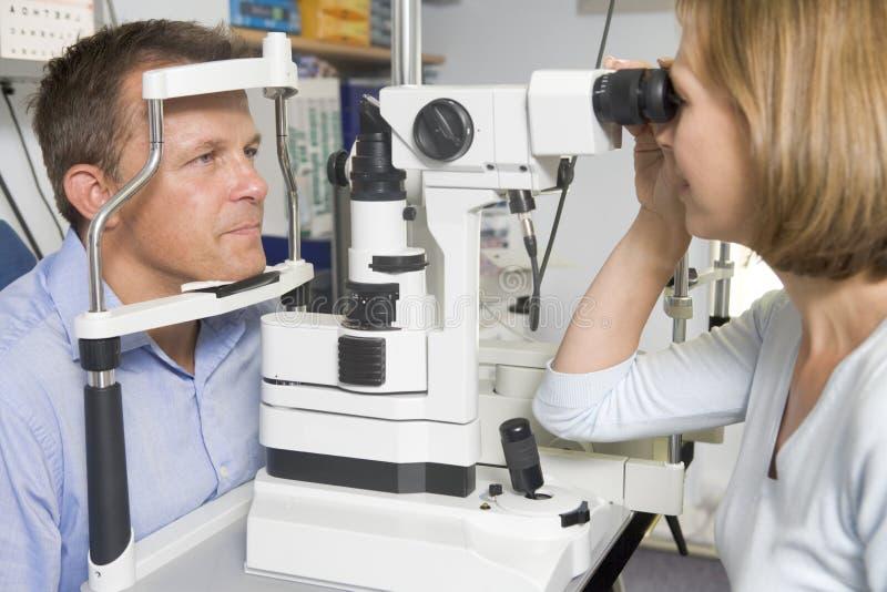 Optometriker im Prüfungraum mit Mann stockfoto