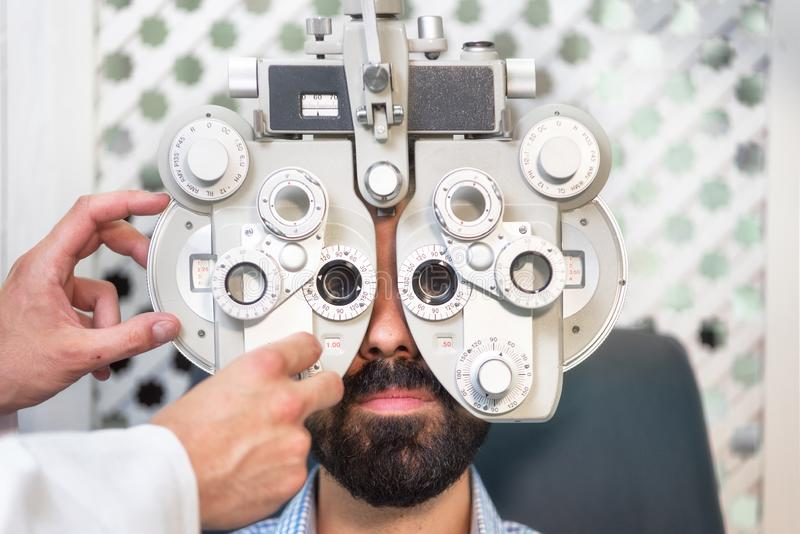 Optometriker som gör sikt som testar för den manliga patienten i klinik Manlig ögonläkare som undersöker den tålmodiga mannen med royaltyfri fotografi