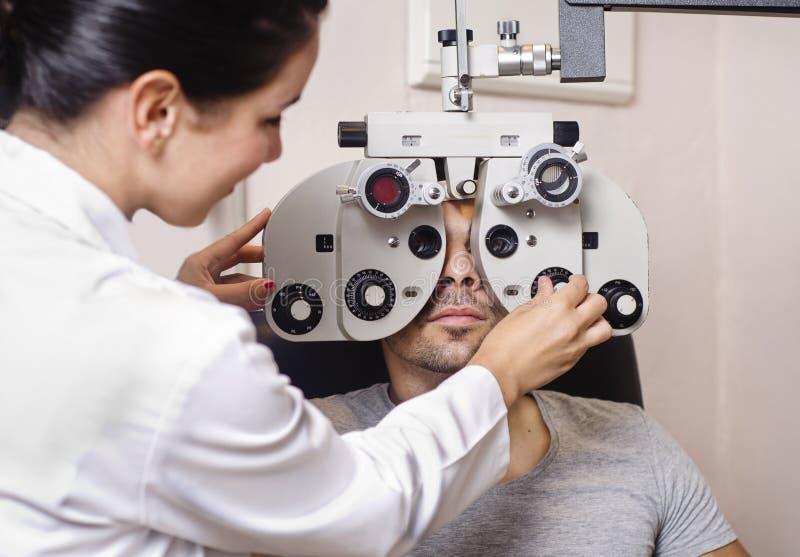 Optometrikerfrau, die phoropter Kalibrierung schaut lizenzfreies stockbild