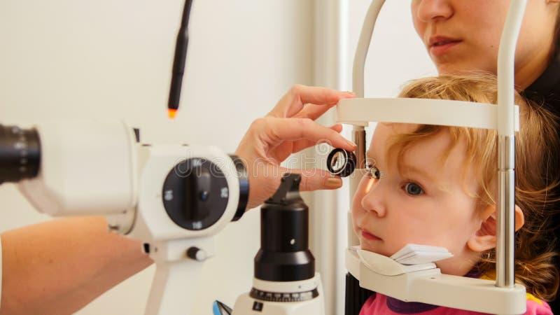 Optometrikerkontrollmädchen ` s Sehvermögen - Mutter und Kind haben Beratung im Augenarztraum stockfotos