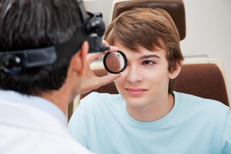 Optometrist выполняя растягиванный ретинальный экзамен стоковая фотография