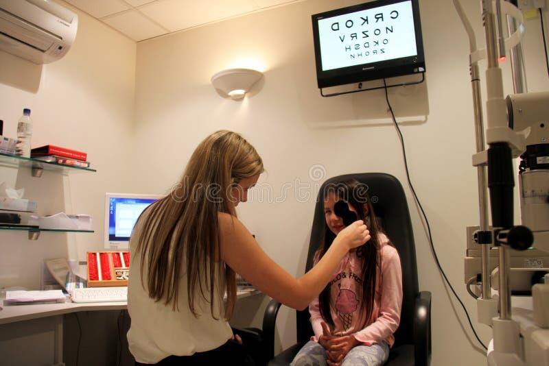 Optometrist проверяя глаза маленьких девочек стоковое изображение