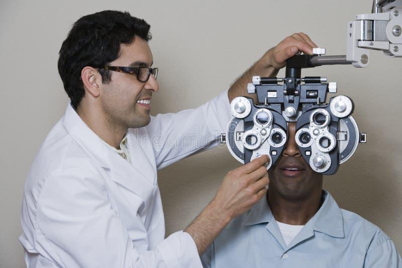 An Optometrist Adjusting Panels Of Phoropter stock images