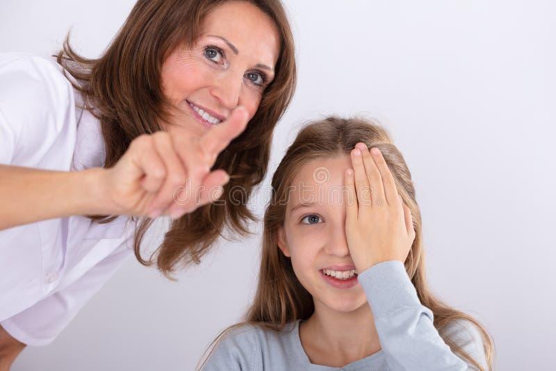 Optometrist Assisting Girl While die Zicht controleren stock afbeelding