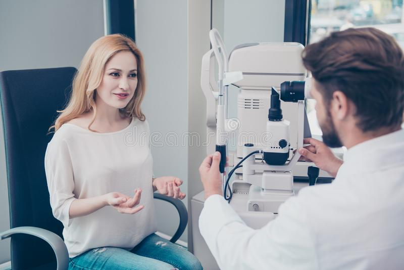 Optometrist consultation. Blond lady patient is talking to brunet bearded male doctor optician in his office about the diagnosis stock photography