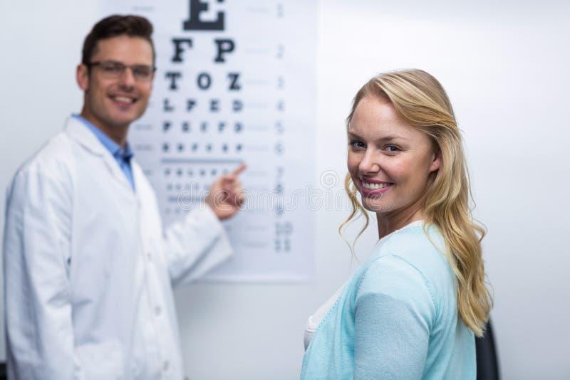 Optometrist die oogtest van vrouwelijke patiënt nemen stock afbeelding