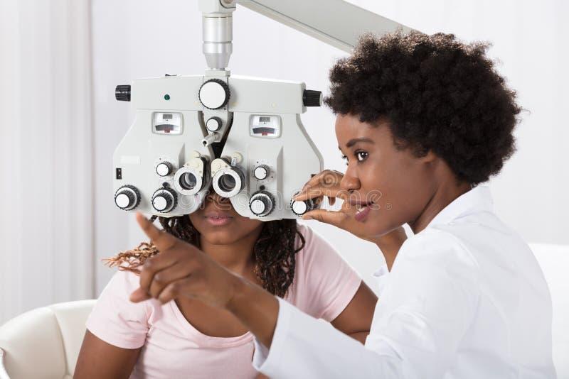 Optometrist Doing Sight Testing voor Patiënt stock afbeeldingen