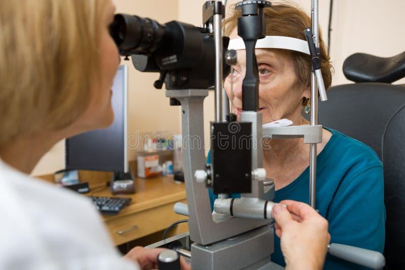 Optometrist Egzamininuje Starszych kobiet oczy obrazy royalty free