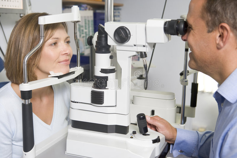 Optometrist in exam room with woman in chair stock image