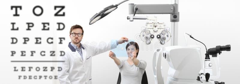 Optometrist examining eyesight woman patient pointing chart at t. Optometrist examining eyesight women patient pointing chart at the hole on plexiglass in royalty free stock image