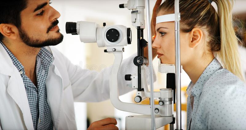 Optometrist examining patient in modern ophthalmology clinic. Optometrist examining patient in ophthalmology clinic with professional equipment stock photos