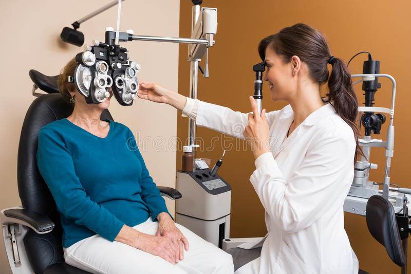 Optometrist Examining Senior Woman's Eyes. Young female optometrist examining senior woman's eyes in store royalty free stock photo
