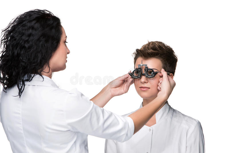 Optometrist holding an eye test glasses and giving. To young women eye examination. Isolate on white background stock photography