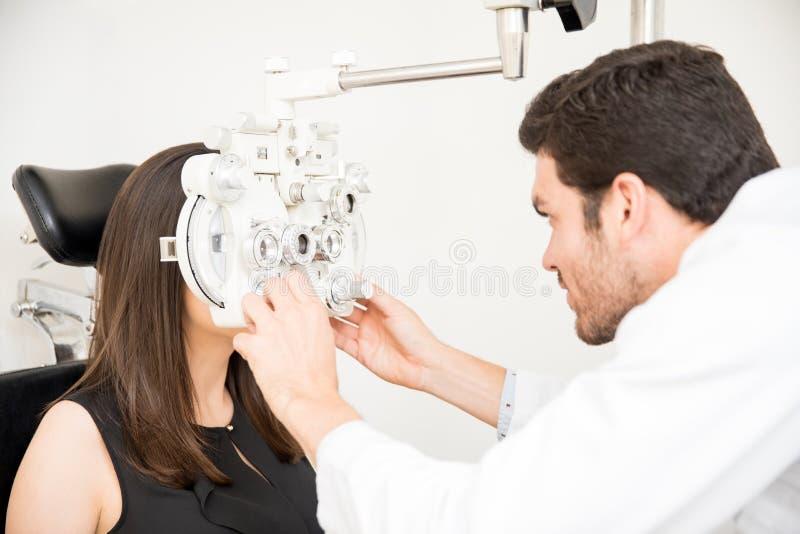 Optometrist i kobieta przy oko egzaminem z phoropter fotografia stock