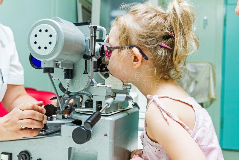 Optometrist met patiënt, die een oogonderzoek geven royalty-vrije stock afbeeldingen