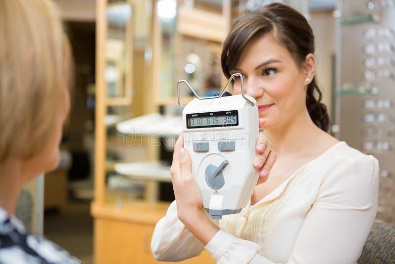 Optometrist Pokazuje Pupilometer Dojrzała kobieta zdjęcia royalty free