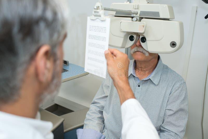 Optometrist przystosowywa phoropter dla starszego męskiego pacjenta obraz stock