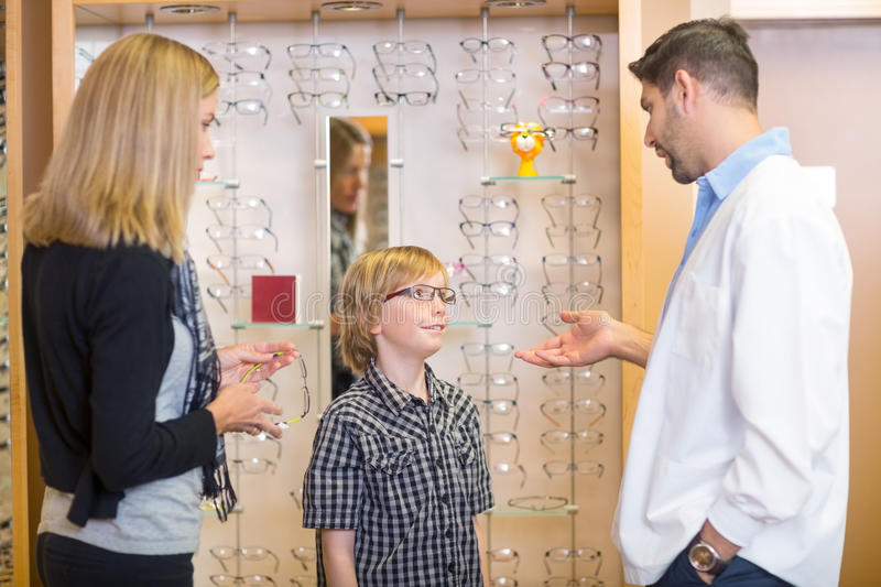 Optometrist Talking To Customers In Store. Mid adult male optometrist talking to customers in store stock photography