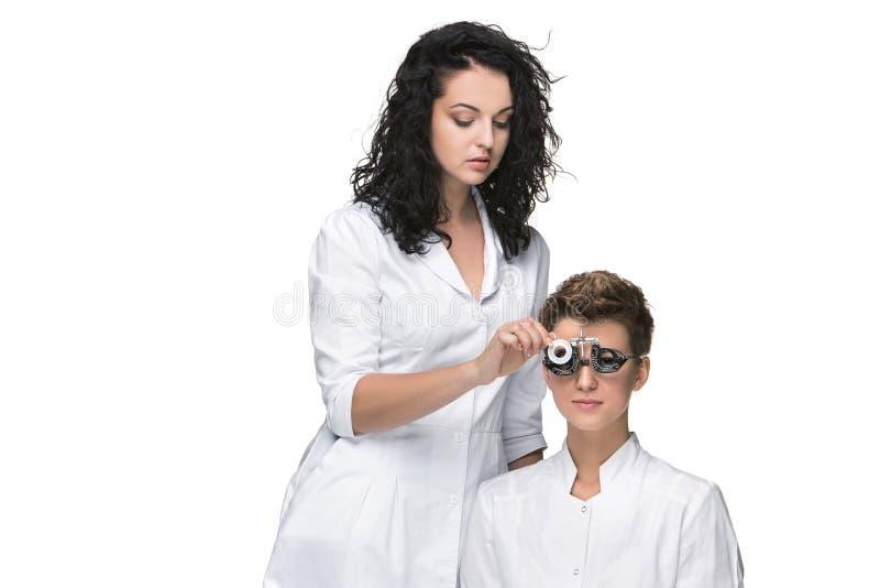 Optometrist trzyma oko testa szkła i daje młoda kobieta egzamin obraz stock