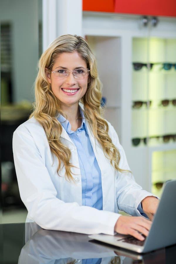 Optometrist używa laptop w okulistyki klinice zdjęcia royalty free