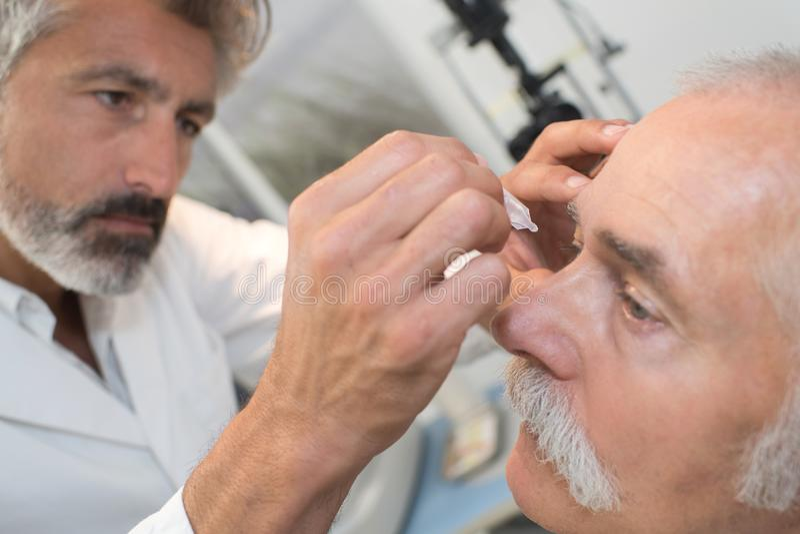 Optometrist using mydriatics eye drops to numb eyes stock photos