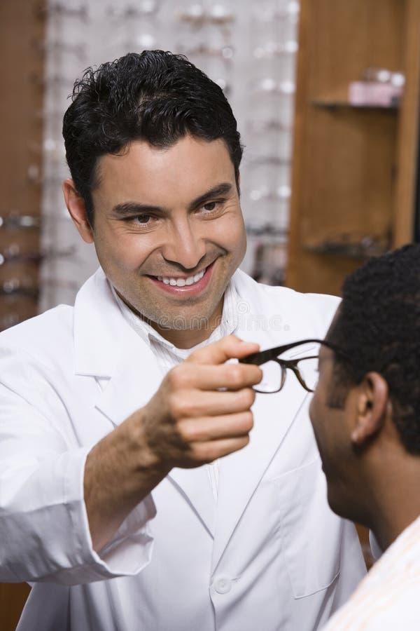 Optometrista Assisting Male Patient em escolher vidros fotografia de stock royalty free