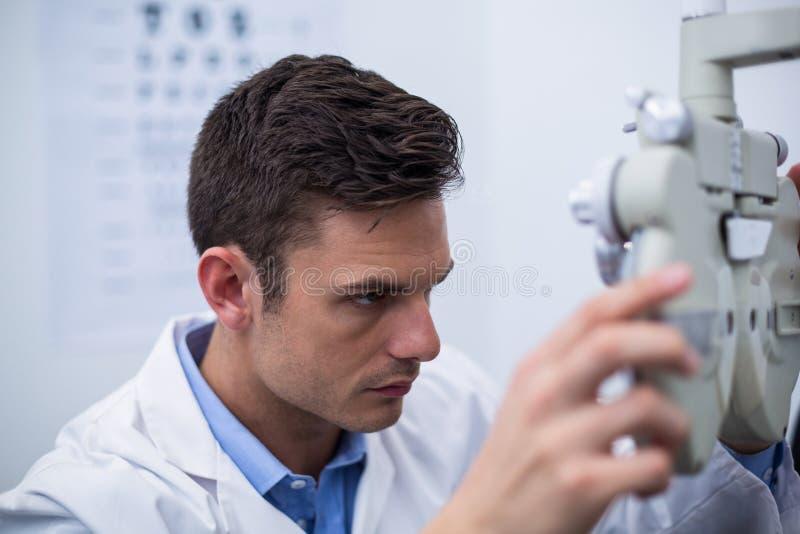 Optometrista attento che guarda attraverso il phoropter fotografia stock