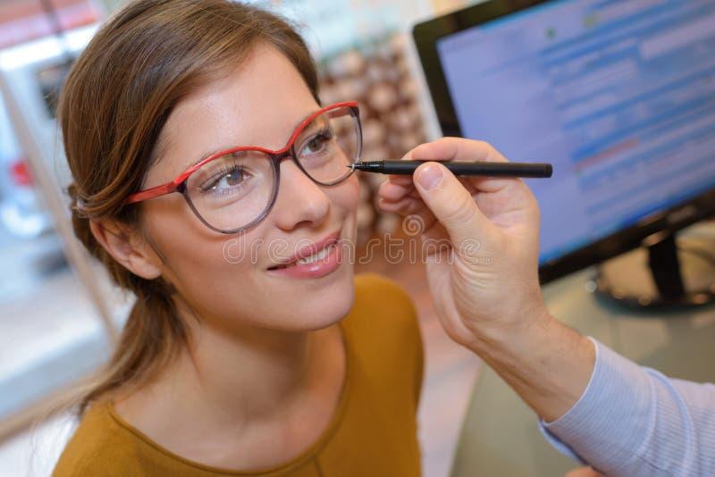 Optometrista che aiuta cliente grazioso ad acquistare gli occhiali fotografie stock libere da diritti