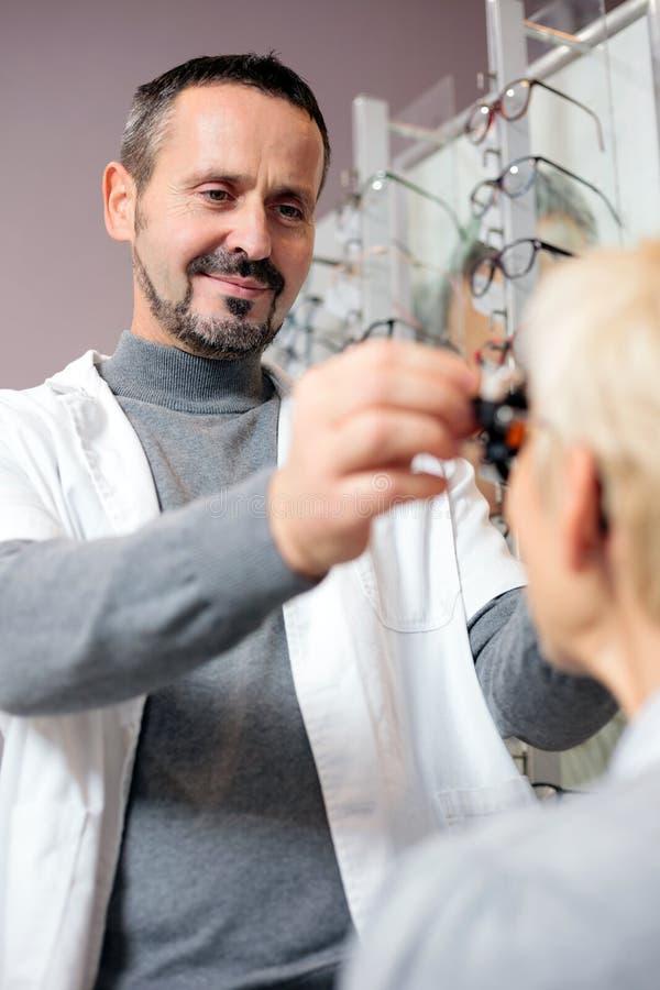 Optometrista de sexo masculino sonriente que examina a la mujer madura, determinando dioptría en clínica de la oftalmología Opini foto de archivo
