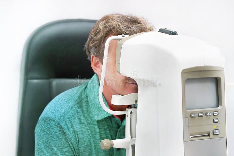 Optometrista Doing Sight Testing per il paziente maschio in clinica fotografia stock libera da diritti