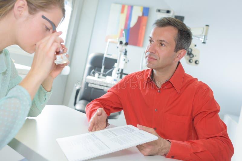 Optometrista femminile che ha discussione con il paziente immagini stock