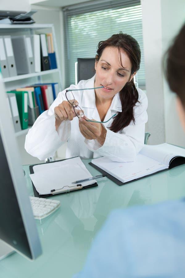 Optometrista grazioso che tiene i vetri in clinica immagini stock libere da diritti