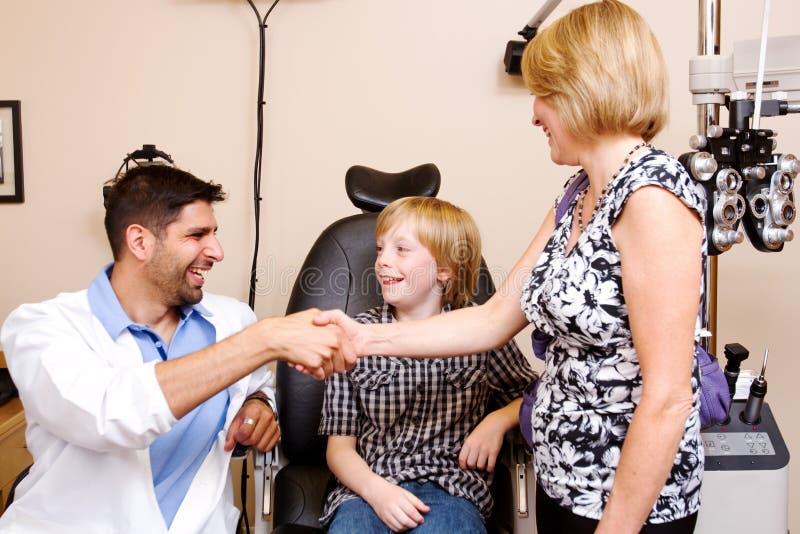 Optometrista, mamã e criança apreciando um riso fotografia de stock