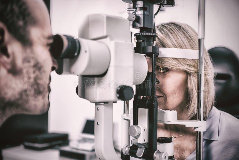 Optometrista que examina o paciente fêmea na lâmpada cortada foto de stock royalty free