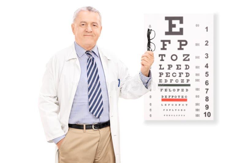 Optometrista que guarda vidros na frente da carta de olho foto de stock royalty free