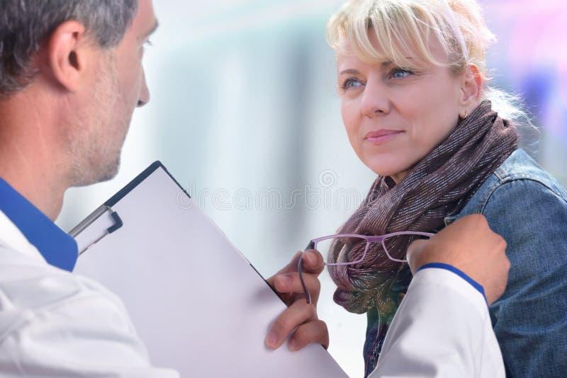 Optometrista que mostra uns vidros a uma mulher fotografia de stock royalty free