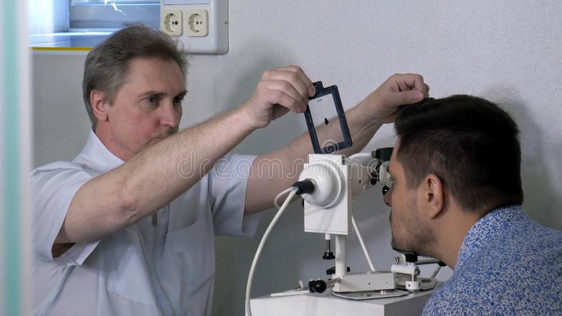 Optometrista superior que faz testes da vista para o paciente imagem de stock