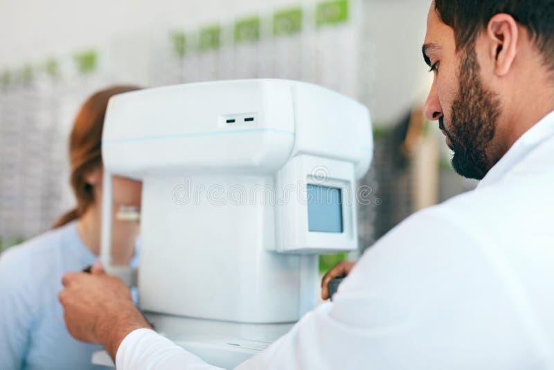 Optometrista Testing Woman Eyesight do teste do olho no equipamento moderno imagem de stock royalty free