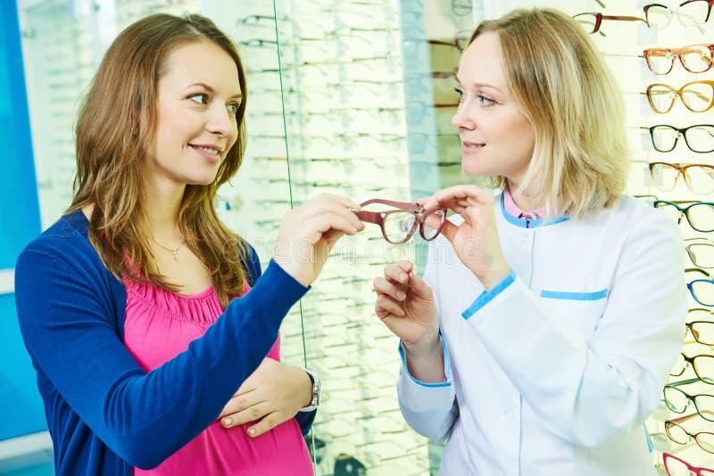 Optometristopticien bij de winkel van oogglazen stock afbeeldingen