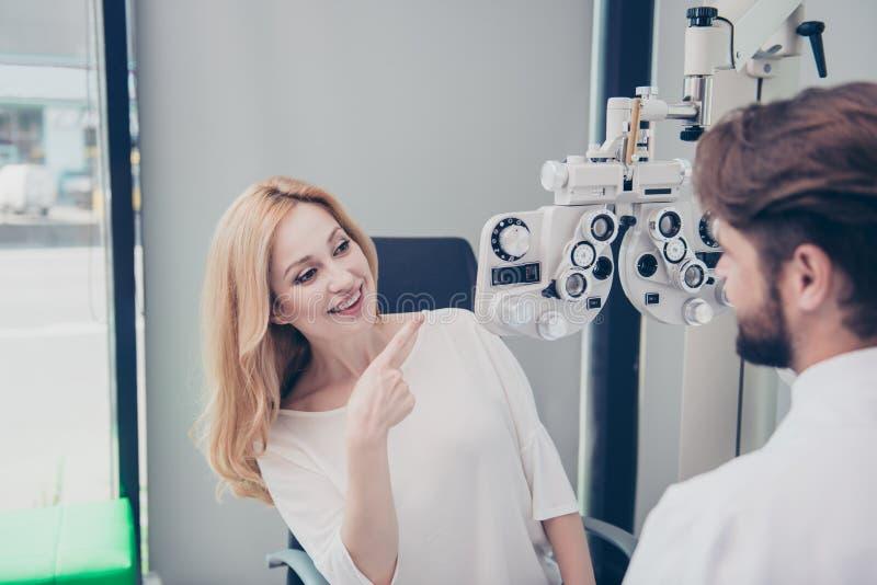 Optometristoverleg De blonde damepatiënt vraagt donkerbruin ben stock fotografie