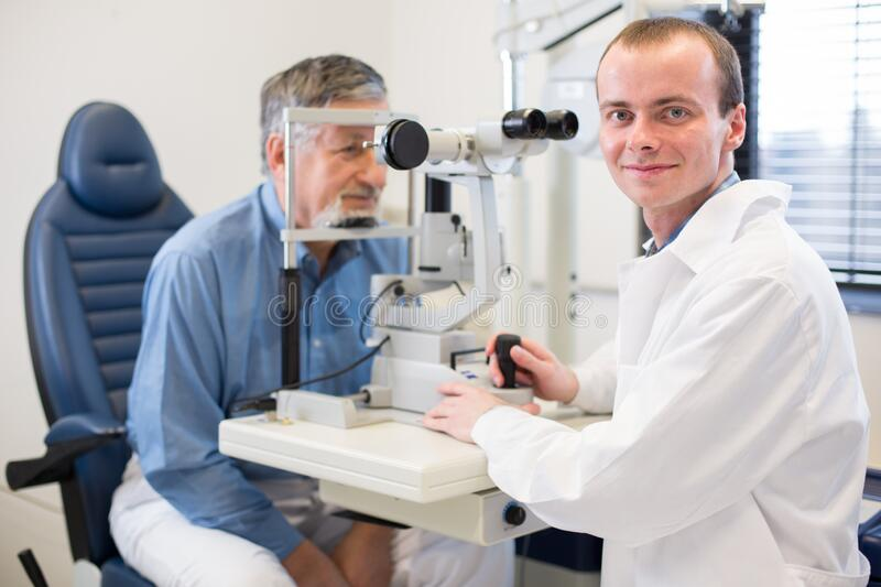 Senior man having her eyes examined by an eye doctor stock image